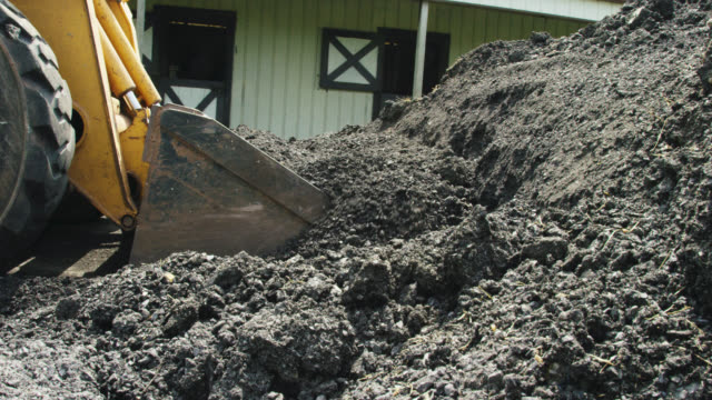 a skid-steer pushes and spreads asphalt around a new driveway in preparation for paving outside a horse barn on a partly cloudy day - material stock videos & royalty-free footage