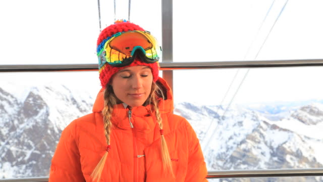 a skier adjusts her goggles as she rides a gondola. - skibrille stock-videos und b-roll-filmmaterial