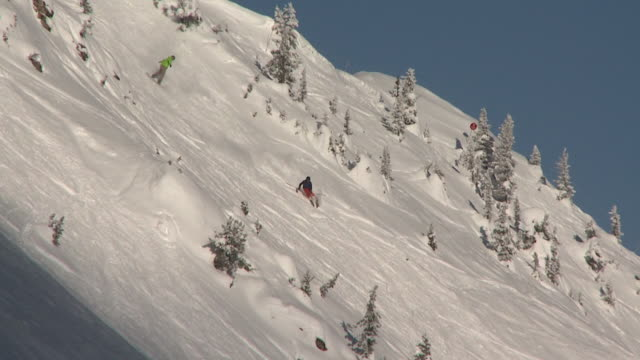 ws ts skier and snowboarder riding down mountain face / golden, british columbia, canada - längd bildbanksvideor och videomaterial från bakom kulisserna