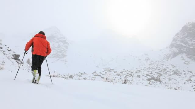 skier ascends slope with snow falling heavily, winter's day - bastoncino da sci video stock e b–roll