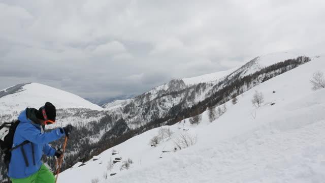 vídeos de stock e filmes b-roll de skier ascends steep snowslope, snowy mtns distant - bastão de esqui