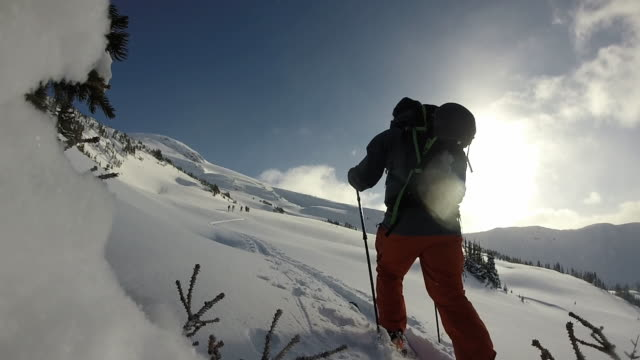 Skier ascends trail up mountain slope, ice crystals