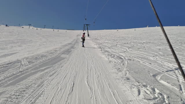skier being pulled up the hill by a small round handheld ski tbar lift, pov - ski lift stock videos & royalty-free footage