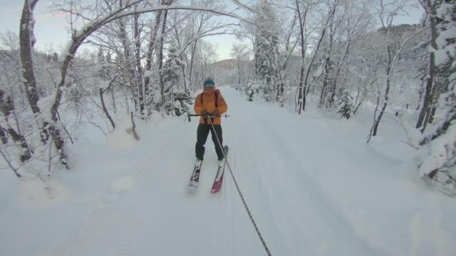 skifahrer geschleppt durch verschneite forststraße - skijacke stock-videos und b-roll-filmmaterial