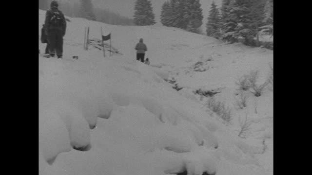 vídeos de stock e filmes b-roll de skier coming down course / shot of village of bad gastein / skier going down street in village / cu two men watching skiers / skier coming down... - roupa de esqui
