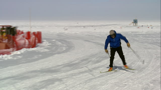ts skier cross country skiing in snow toward geodesic dome / antarctica - ski pole stock videos & royalty-free footage