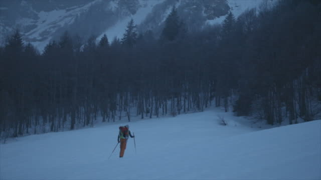 A skier cross country skis up a mountain in the snow.