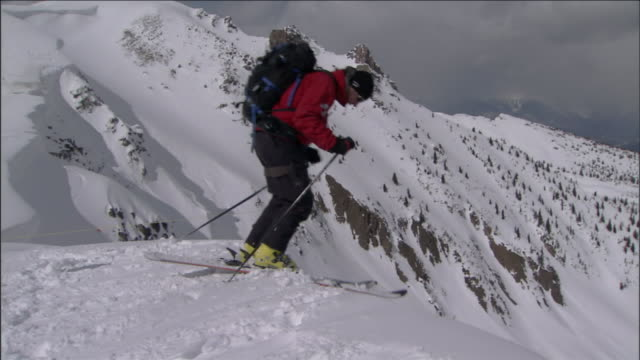 a skier disappears down a steep hill on a snow-covered mountain slope. - ski holiday stock videos & royalty-free footage