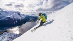 Skier doing powder turn above Norwegian fjord