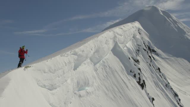 vídeos de stock, filmes e b-roll de skier drops into steep line in alaska - snow cornice