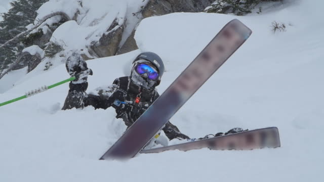 skier falls crashes and gets buried in fresh powder snow while skiing in the mountains. - slow motion - powder snow stock videos & royalty-free footage