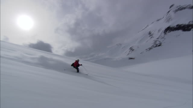 a skier glides down a snowy slope. - downhill skiing stock videos & royalty-free footage