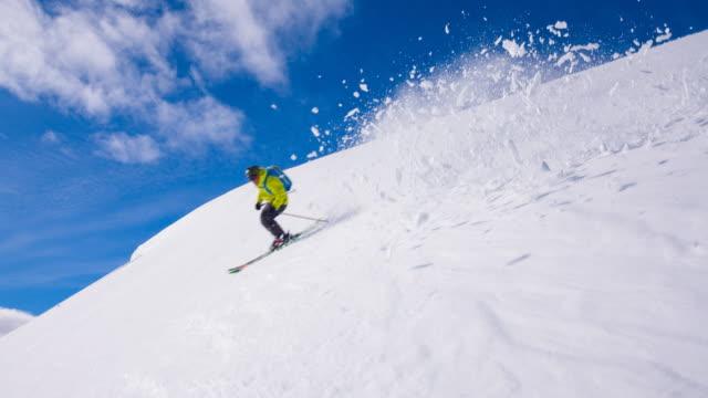 skidåkare kommer ner från berget, rider nyfallen snö - freestyleskidåkning bildbanksvideor och videomaterial från bakom kulisserna