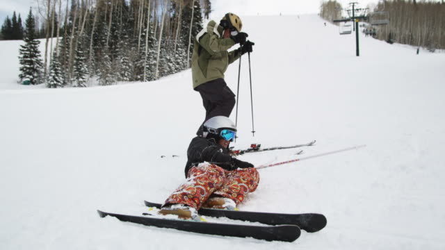 skier helping a fallen skier up - park city utah video stock e b–roll