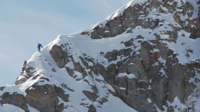 WS Skier hiking up snowcapped mountain / Alta, Snowbird, Utah, USA