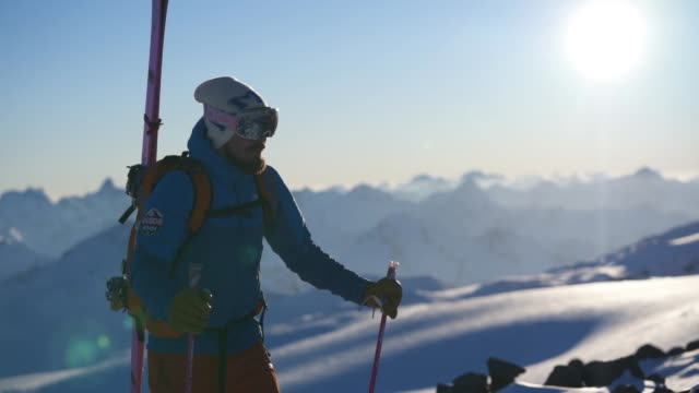 skier hiking upa mountain slope with sun behind - solo uomini giovani video stock e b–roll