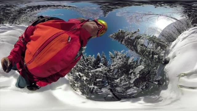 Skier holding 360 action camera descends snowy powder run through forest