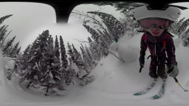 Skier holding 360 action camera descends snowy powder run through forest