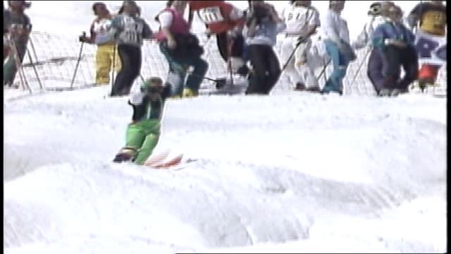 vídeos de stock e filmes b-roll de skier in neon green snow pants riding down mountain in killington vermont - roupa de esqui