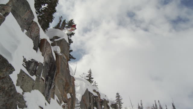 ws td slo mo skier jumping off big cliff / alta, snowbird, utah, usa - alta utah stock videos and b-roll footage