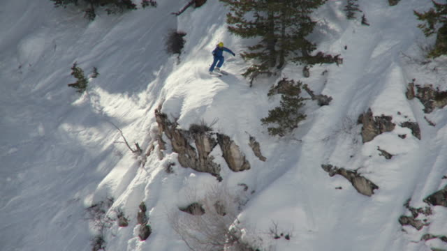 WS TD SLO MO Skier jumping over rocks on choppy slope / Alta, Snowbird, Utah, USA