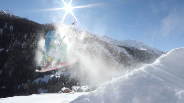 skier jumps above swiss village after fresh snow - ski jacket stock videos & royalty-free footage