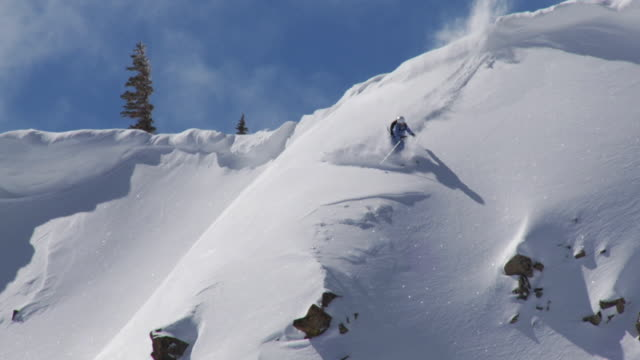 ws td zo tu slo mo skier jumps off cliff and lands in powder / alta, snowbird, utah, usa - alta utah video stock e b–roll