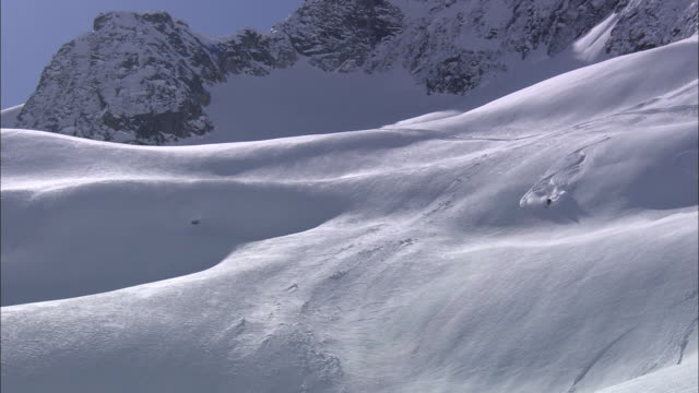 a skier leaves a trail as he speeds down a steep, snowy mountainside. - rocky mountains stock videos & royalty-free footage