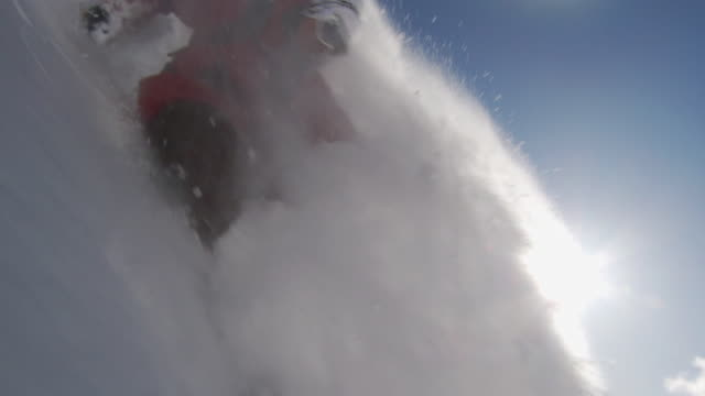 MS SLO MO Skier making slash turn, sun shining in background / Alta, Snowbird, Utah, USA