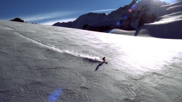 AERIAL WS TS Skier moving across slope with mountains and shining sun in background / Switzerland