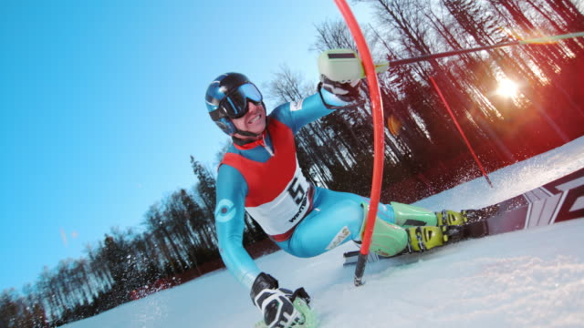 slo mo ld skier passing a slalom pole in a race - competizione video stock e b–roll