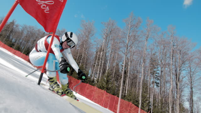 slo mo skier passing the gate at giant slalom race - ski slope stock videos & royalty-free footage