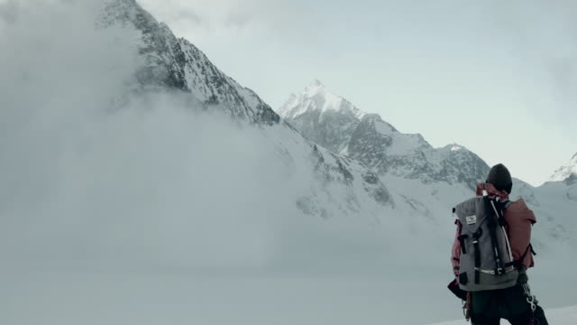 Skier pointing at mountains in the snow in Swiss Alps.