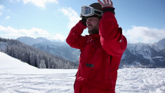 skier putting on helmet and goggles and moving off - skibrille stock-videos und b-roll-filmmaterial