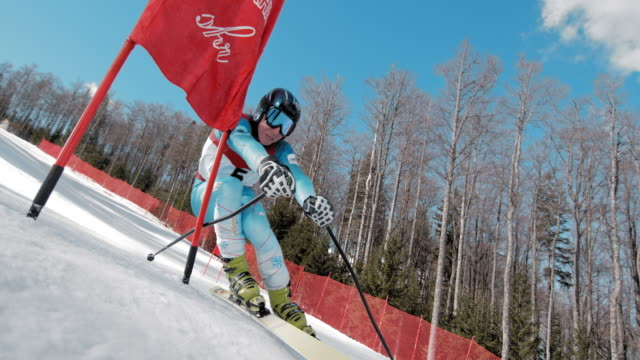 slo mo skier racing through the gate at a giant slalom race - ski slope stock videos & royalty-free footage