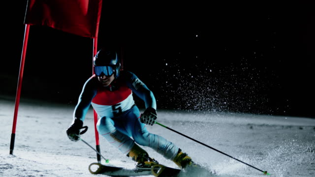 SLO MO Skier racing through the gate at a night giant slalom race