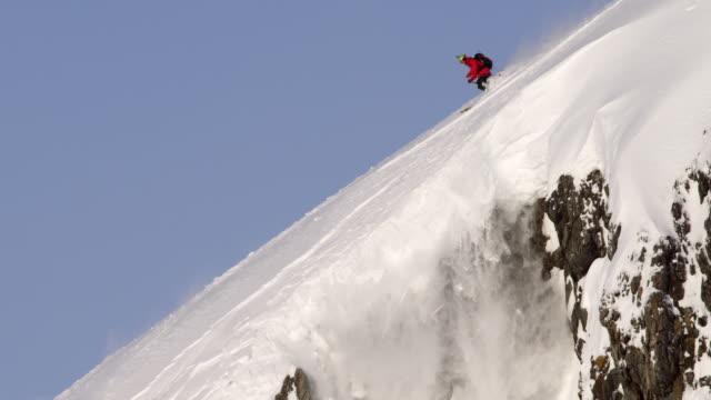 skier rides down edge of steep cliff - bastoncino da sci video stock e b–roll