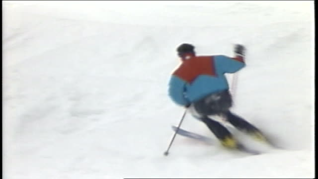skier riding down hill away from camera in killington vermont - スキーウェア点の映像素材/bロール