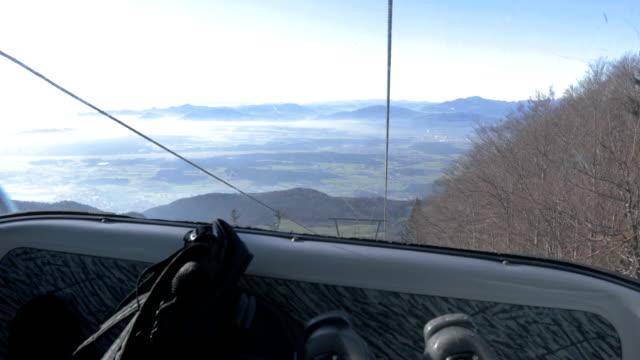 skier riding in overhead cable car to the top of mountain - inquadratura dalla sciovia video stock e b–roll