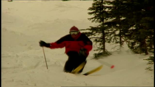 vídeos de stock e filmes b-roll de skier riding over snowy hills in telluride colorado - roupa de esqui