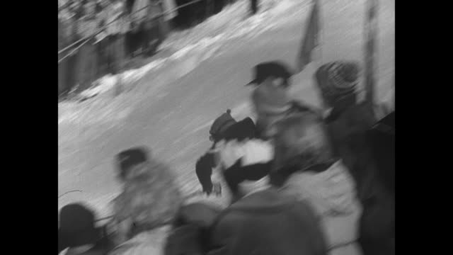 Skier runs slalom course in men's slalom event at Winter Olympics crowds line the course / skier falls during slalom run / various shots of skiers...