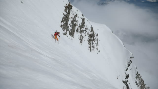 A skier skiing down a steep mountain in the snow.