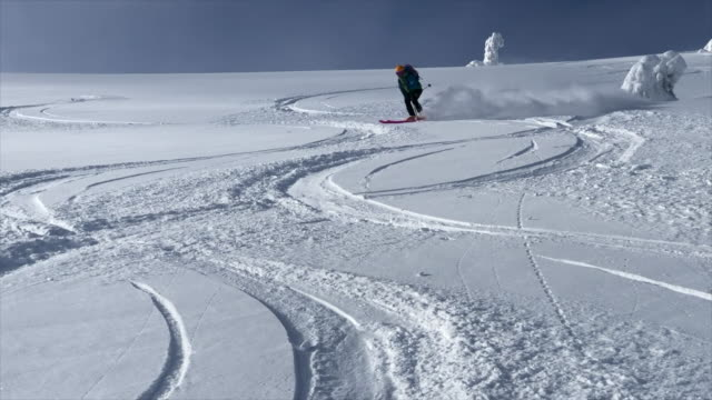 A skier skiing downhill on a snow covered mountain in fresh powder snow. - Slow Motion