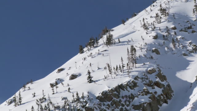 WS TU TD ZO Skier skiing in aqua skis while chased by avalanche / Alta, Snowbird, Utah, USA