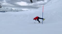 Skier skiing on mountain ski on springboard at snowy slope slow motion. Skier riding on ski and falling on mountain slope. Winter sport. Winter activities. Extreme sport concept