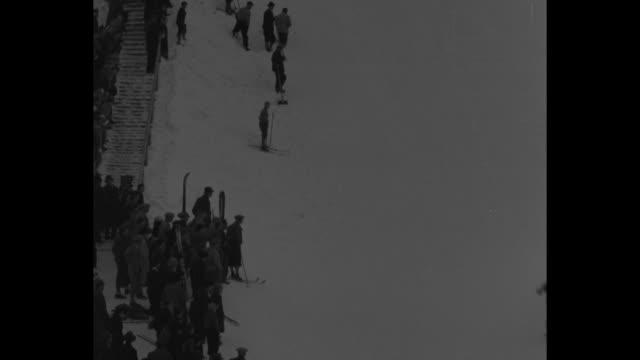 vs skier speeds past camera during skiing at garmischpartenkirchen flies in air lands at bottom of ski jump falls at end of course skier on long... - garmisch partenkirchen stock videos and b-roll footage