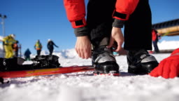Skier stepping into the ski bindings with his ski boots on a sunny morning.
