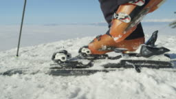 SLOW MOTION CLOSE: Skier steps into the ski bindings with ski boots on the piste
