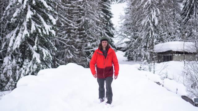 skifahrer geht in richtung kamera durch verschneiten wald - eskapismus stock-videos und b-roll-filmmaterial