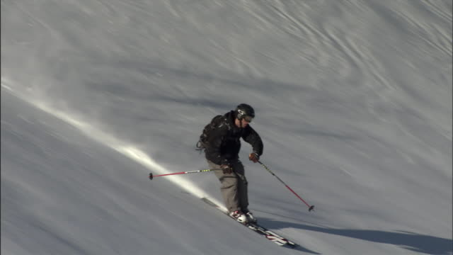 a skier with a backpack navigates cautiously over fresh snow. - downhill skiing stock videos & royalty-free footage
